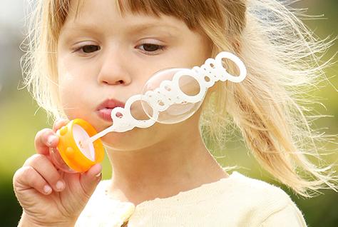 litte girl blowing bubbles