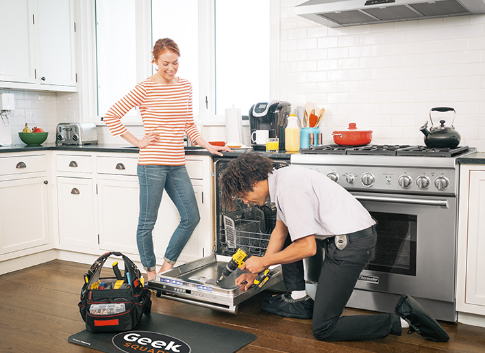 Geek Squad Agent repairing dishwasher, client