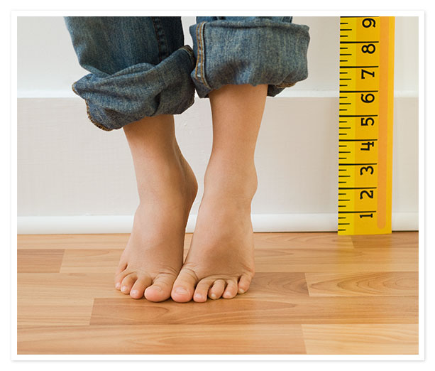 Child's feet next to measuring stick