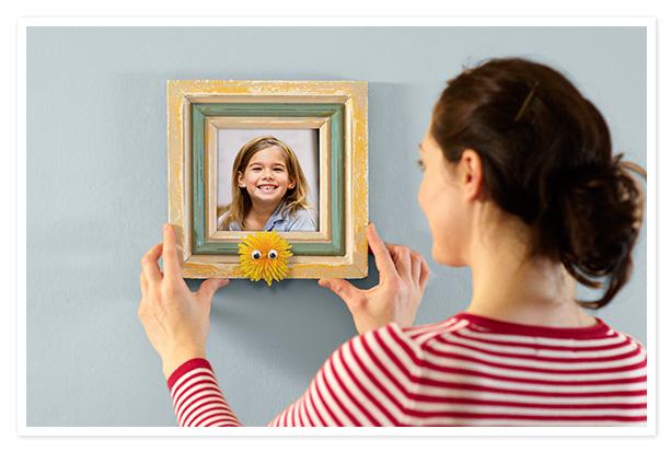 Mom hanging framed photo of kids