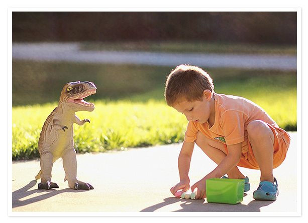 Child outside with dinosaur toy
