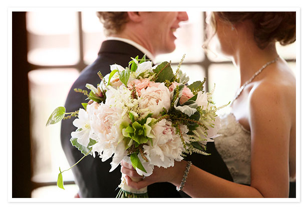 Bride holding flowers with groom