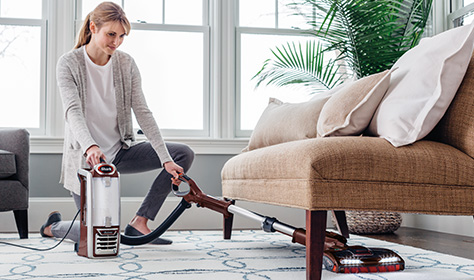 Woman vacuuming under couch